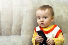 看对智能手机的一个小男孩说谎在长沙发 库存照片