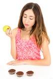 看对松饼的饮食的妇女,当吃苹果时 免版税库存照片