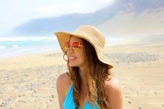 看对海的美丽的时尚妇女在她的假日兰萨罗特岛 有太阳镜和草帽的愉快的女孩在海滩 库存图片