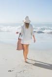 看对海的sunhat运载的海滩袋子的白肤金发的妇女 库存图片