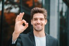 看对照相机和显示在办公楼背景的成功的愉快的人好标志 专业男性经理 库存图片
