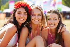 看对照相机的音乐节的三个女朋友 免版税库存图片