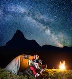 看对的两个游人在野营的发光的帐篷附近发光满天星斗的天空和银河在晚上在营火附近 库存图片