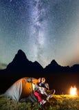 看对的夫妇恋人在野营的照明设备帐篷附近发光满天星斗的天空和银河在晚上在营火附近 库存照片