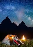 看对的浪漫夫妇远足者在晚上发光满天星斗的天空和银河在野营靠近营火 免版税库存图片