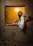 看对窗口和红色太阳的白色礼服的肉欲的夫人在她后 免版税图库摄影