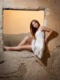 看对窗口和红色太阳的白色礼服的肉欲的夫人在她后 免版税库存照片