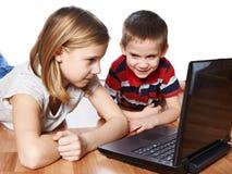 看对膝上型计算机的姐妹和兄弟 库存图片