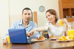 看对膝上型计算机的愉快的夫妇在早餐期间 免版税库存图片