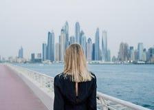 看对迪拜小游艇船坞风景的美丽的妇女 免版税库存照片