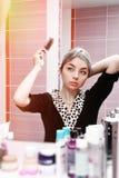 看对镜子和梳她的头发的年轻白肤金发的妇女 免版税图库摄影