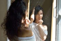 看对镜子的性感的美丽的妇女窗口 免版税库存图片