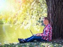 看对他的膝上型计算机的年轻人在室外城市的公园 库存图片