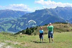看对滑翔伞的成人和孩子飞行在美丽的山和谷 免版税库存照片