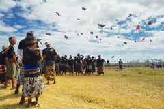 看小组飞行风筝的巴厘语人 免版税库存照片