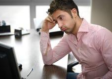 看屏幕的疲乏或沮丧的办公室工作者 免版税库存照片