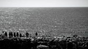 看岩层的人们海 免版税库存照片