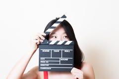 看左与clapperboa的年轻美丽的亚洲妇女特写镜头 库存照片