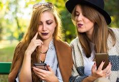 看巧妙的电话的女性朋友公园 免版税库存图片