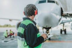 看巨大的飞机的红色耳机的工作者 免版税库存照片