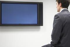 看平面屏幕电视的商人 免版税库存图片