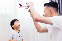 看平面玩具和使用与父亲的好奇孩子 一起演奏玩具的亚洲家庭在家 库存照片