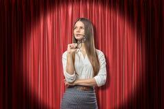看年轻的女实业家认为和,拿着玻璃在嘴唇附近,站立在聚光灯在红色阶段帷幕附近 免版税图库摄影