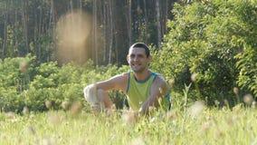 看年轻英俊的快乐的人画象坐草本质上在森林背景的夏天和  影视素材
