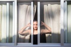 看开窗口的妇女 免版税库存图片