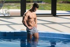 看强壮男子的人的年轻人旅馆室内游泳池 免版税图库摄影