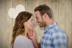 看彼此和微笑的愉快的年轻夫妇的综合图象 库存照片