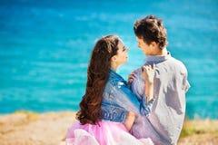 看彼此的一对愉快的年轻夫妇的画象一起享受一天在海附近 免版税图库摄影