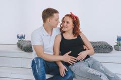年轻看彼此的人和美丽的孕妇 预期婴孩 将来的父项 图库摄影