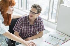 看彼此的企业夫妇,当使用膝上型计算机在创造性的办公室时 免版税库存照片