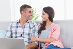 看彼此的夫妇,当使用膝上型计算机时 免版税库存照片