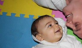 看彼此的婴孩和父亲在colorfull playmat 免版税库存图片