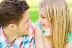 看彼此的微笑的夫妇在公园 免版税库存图片