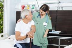 看彼此的患者和护士在康复中心 库存照片