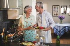 看彼此的愉快的资深夫妇一起准备食物在厨房里 免版税库存图片