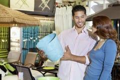 看彼此的愉快的年轻夫妇,当拿着一份纪念品的人在商店时 免版税库存图片
