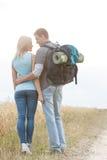 看彼此的浪漫远足的夫妇背面图,当站立在领域时 库存照片