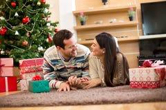 看彼此的爱恋的夫妇在圣诞树附近 免版税库存照片