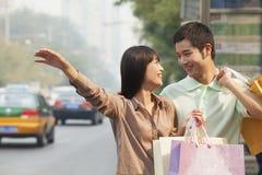 看彼此的年轻夫妇与称赞一辆计程车的购物袋在北京 库存图片