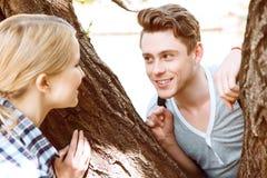 看彼此的年轻夫妇在树之间 免版税库存照片