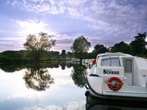 看往与小船的日落由河岸停泊了 库存照片