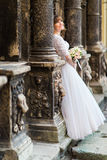看往在老大厦和藏品新娘花束之间的专栏的美丽的年轻新娘 库存照片
