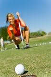 看往杯的女性高尔夫球运动员球辗压 库存照片