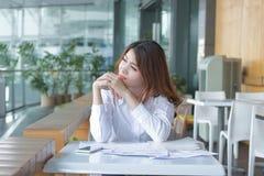 看很远办公室的轻松的年轻亚裔雇员画象  免版税库存图片