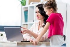 看微笑的母亲的小女孩使用膝上型计算机在工作场所 免版税库存照片
