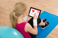 看心脏在数字式片剂的妇女脉搏率 免版税库存照片